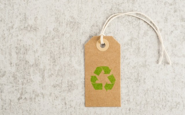 Recycling symbol on brown paper tag. Concept of environmental awareness, eco lifestyle and green eco-friendly shipping.