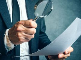 Tax inspector investigating financial documents through magnifying glass, forensic accounting or financial forensics, inspecting offshore company financial papers, documents and reports.